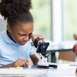 young girl looking through microscope in science class