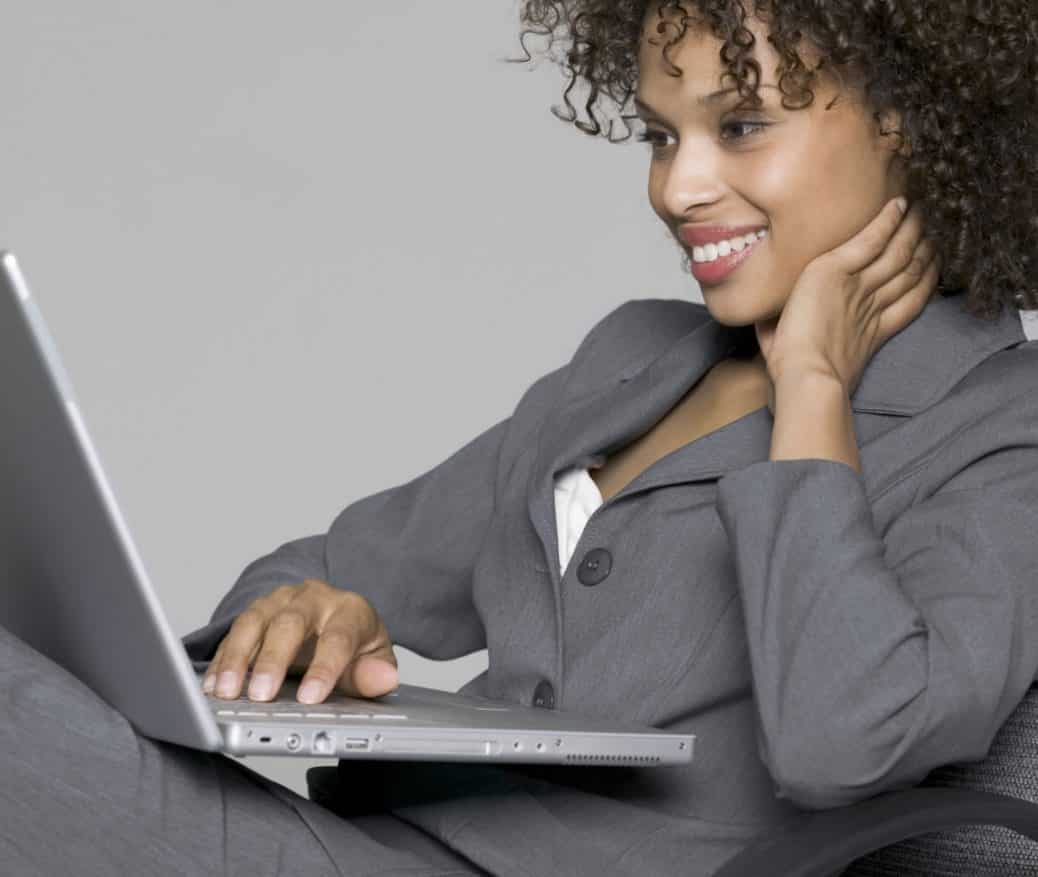 Woman on her laptop in a suit smiling