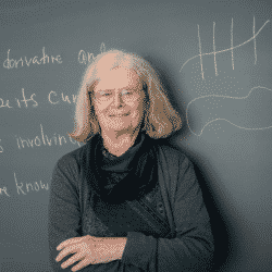 Karen Uhlenbeck stands in front of chalkboard that has mathematical drawings on it, with her arms folded wearing a green sweater