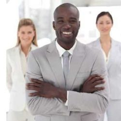 Man in suit with co-workers behind standing looking confident