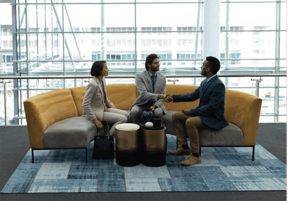 three professional people seated on a gold round work couch with one man shaking interviewers hand after job interview