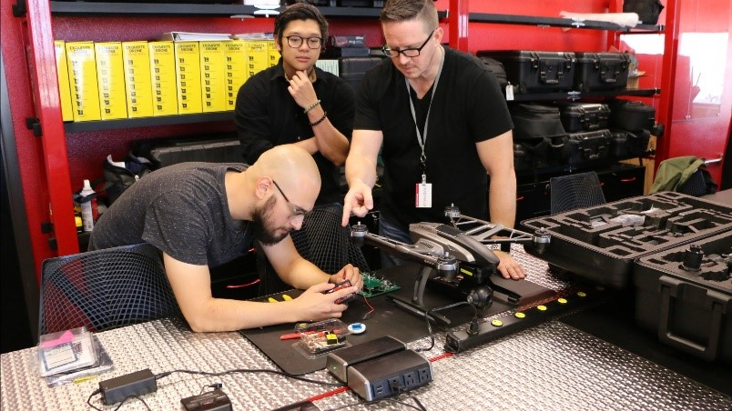 3 people are pictured working on a drone project at the NAIS, Arise workshop activity