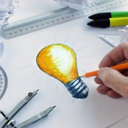 man drawing a design on paper with a pencil