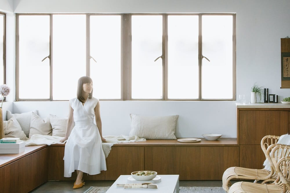 Marie Kondo dressed in all white seated in front of a bright window with sparce livingroom furniture