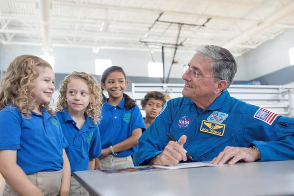grade school children visiting with former astronaut