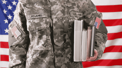 veteran student holding books in his arm with flag in the background