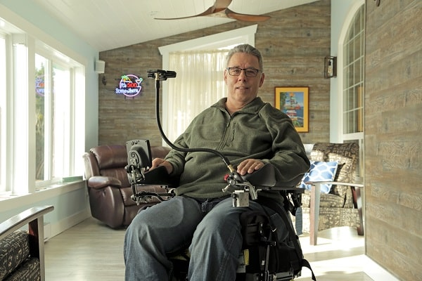 Jim Ryan, male, sitting in his HOOBOX Robotics' Wheelie 7 wheelchair in his living room, smiling for the camera