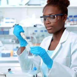 African-american scientist or graduate student in lab coat and protective wear works in modern laboratory