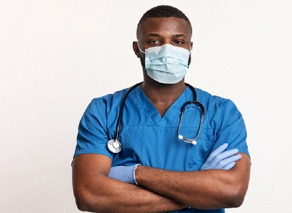 Confident black doctor in healthcare face mask and gloves