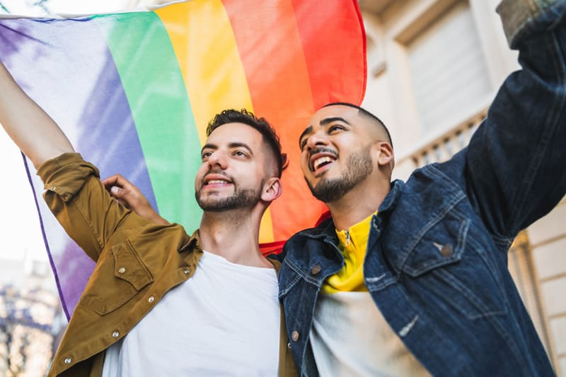 Two lgbtq men holding a rainbow flag with their arms around each other