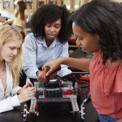 Three girls working on an engineering project in a science lab