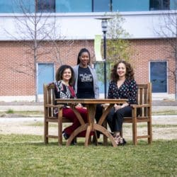 three black women nuclear engineers seated at table on the grass outside office building