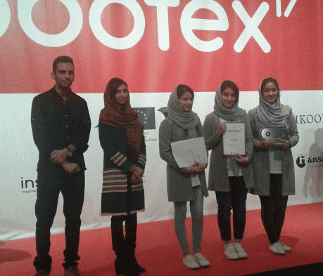 Four Afghanistan teen girls on stage accepting their robotics award