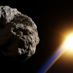 Stock image of an asteroid in space with earth sitting behind it.