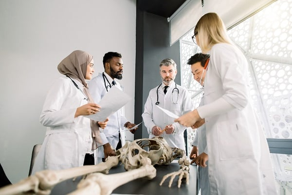 A group of diverse scientists studying a skeleton