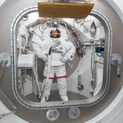 NASA astronaut Jeanette Epps trains in a spacesuit within a mock International Space Station model at NASA's Johnson Space Center