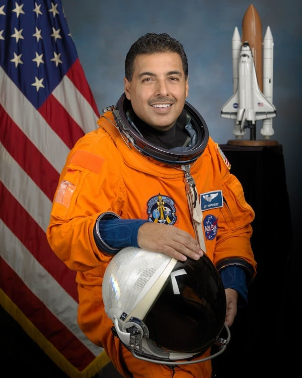 Astronaut Jose Hernandez in spacesuit smiling holding his space suit helmet