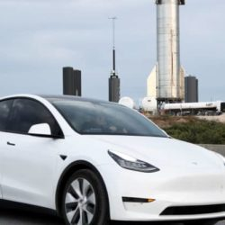 Photo of a white tesla on the road with factory in the background
