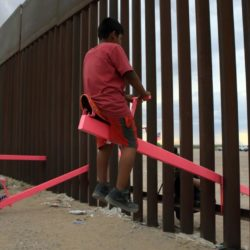 Young hispanic boy sitting on a teeter totter at the border wall with a man on other side an the end of it