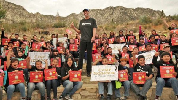 Kareem Abdul-Jabbar with students at his Skyhook Camp cheering and holding up posters of their camp flyer