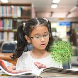 """Young girl in library reading textbook with the tree of knowledge growing out of the textbook with the caption """"education"""""""