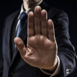 professional man in a suit with his hand extended projecting stop with a hand signal