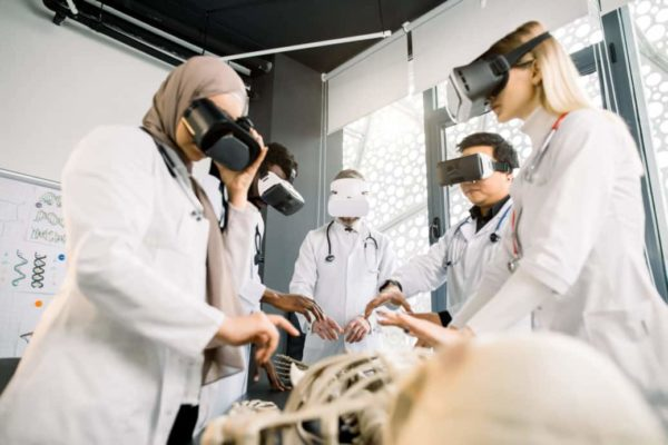 Shot of male professor and four medical students wearing VR goggles and studying human bones anatomy. Multiethnical team of doctors exam human