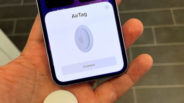 a persons hand holding the iphone with the air tag app on the screen