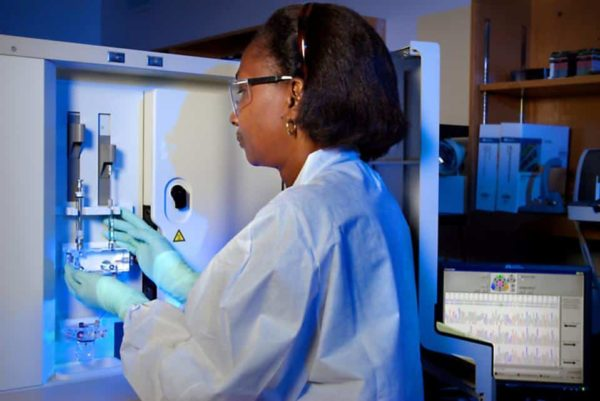 Dr. Karidia Diallo in a laboratory setting at the CDC, in front of an ABI DNA Analyzer