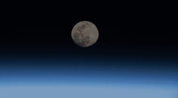 Image of the moon in space hovering over the atmosphere