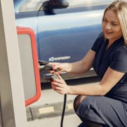 Woman kneeling down to charge her electric car