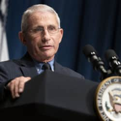 Dr Anthony Fauci standing behind a podium speaking with an american flag behind him