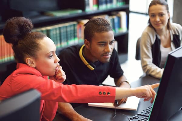 diverse students looking at computer screen in a college classroom environment