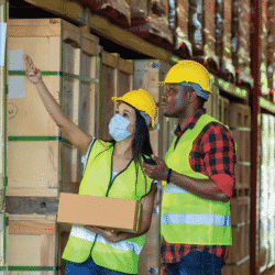 A man and woman look at inventory in a manufacturing warehouse