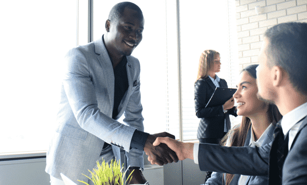 man in a suit and tie shaking hands with a hiring manager
