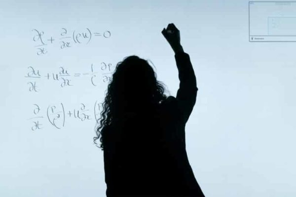 Woman writing physics equations on a white board
